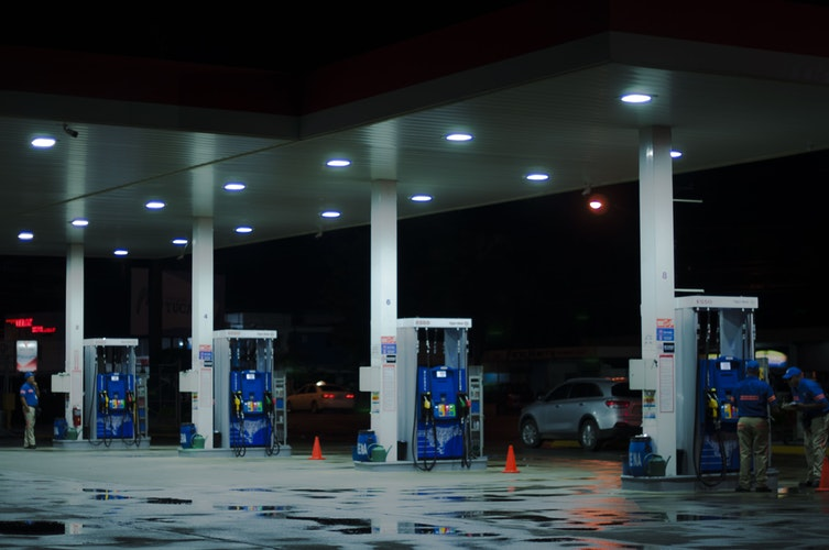 person taking a photo of blue and white gasoline station - The Bright Side of using Fossil Fuel in Modern Times